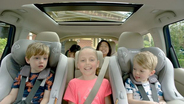 SUV interior with 5 kids sitting in 2 rows of seats