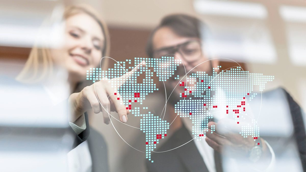 Two people pointing at a world map