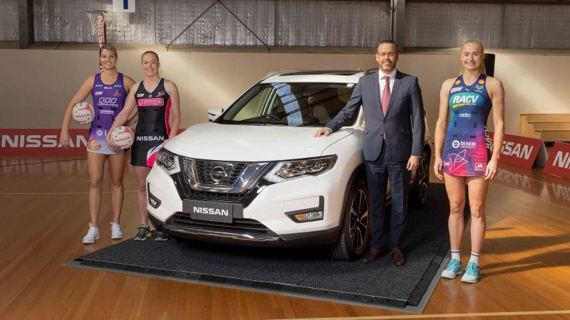 Gretel Tippett, Hannah Petty, Stephen Lester, and Jo Weston on netball court standing next to Nissan QASHQAI