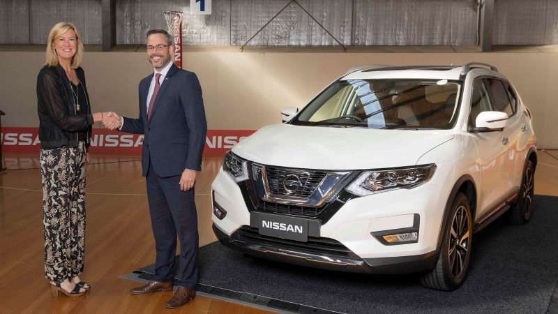 Netball Australia CEO Marne Fechner and Nissan Australia managing director Stephen Lester shaking hands on netball court in front of Nissan QASHQAI