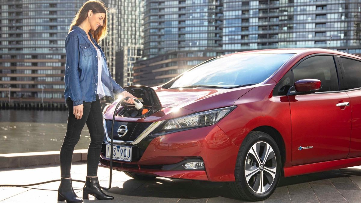 Woman plugging in Nissan LEAF