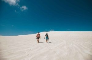 two people walking through sand hills