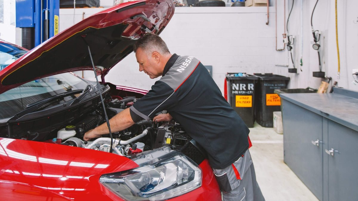 Nissan mechanic servicing vehicle