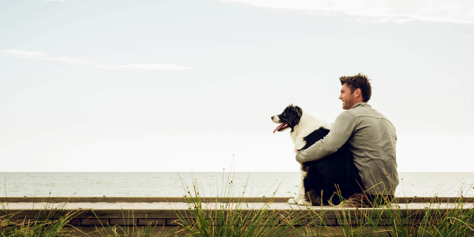 Man and dog relaxing on coastline