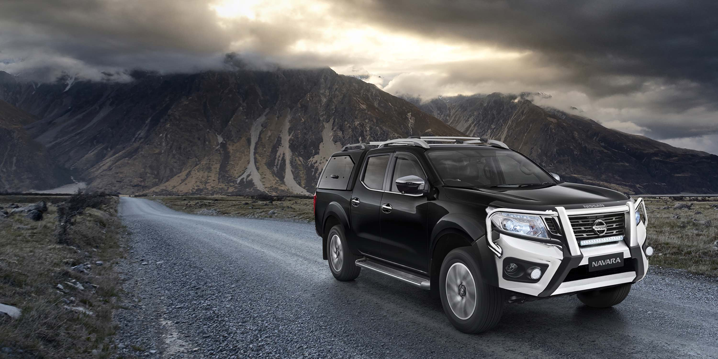 Accessoriesed Nissan Navara driving in front of stormy mountain range