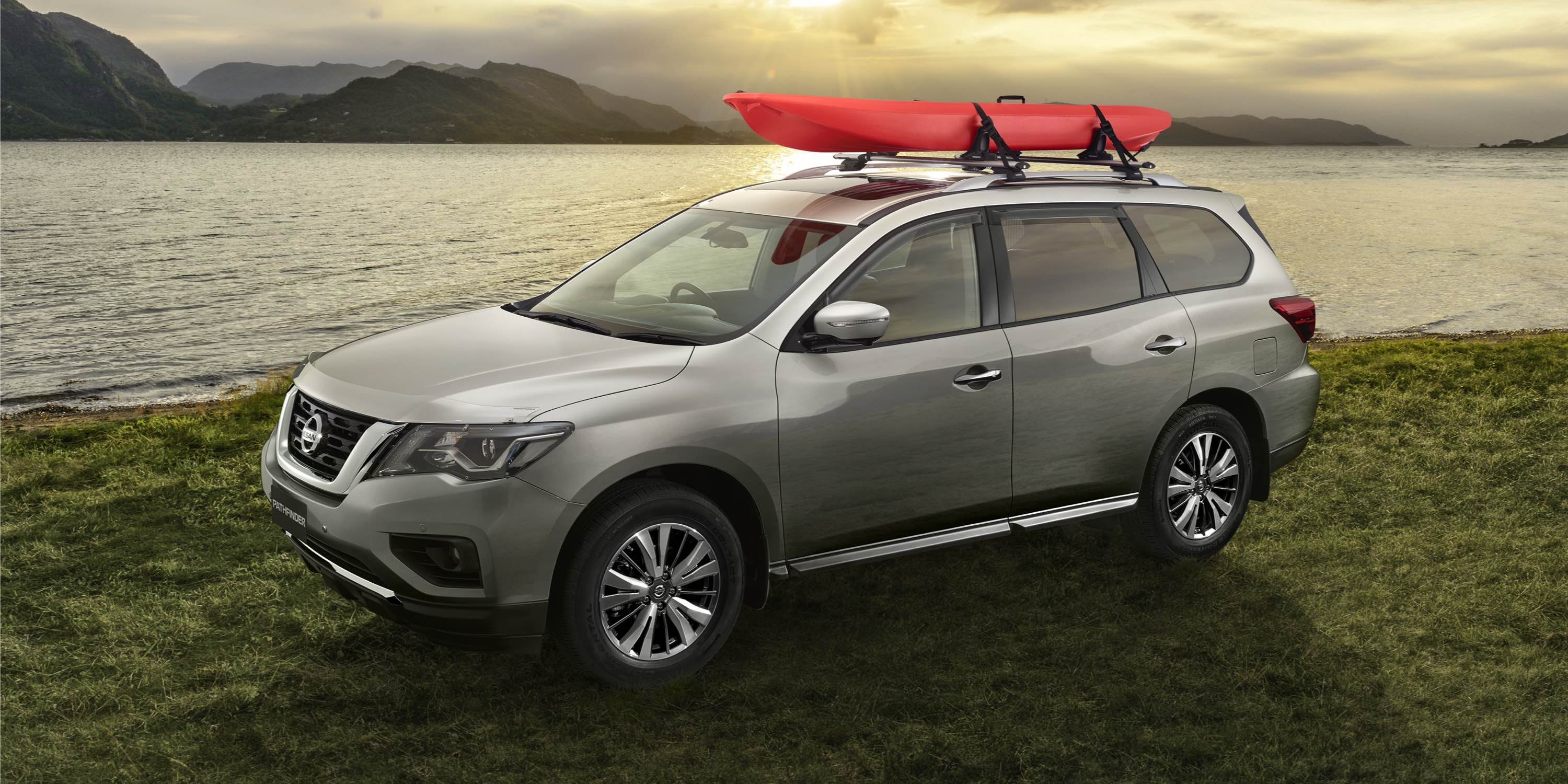 Nissan Pathfinder carrying kayak parked next to a peaceful lake