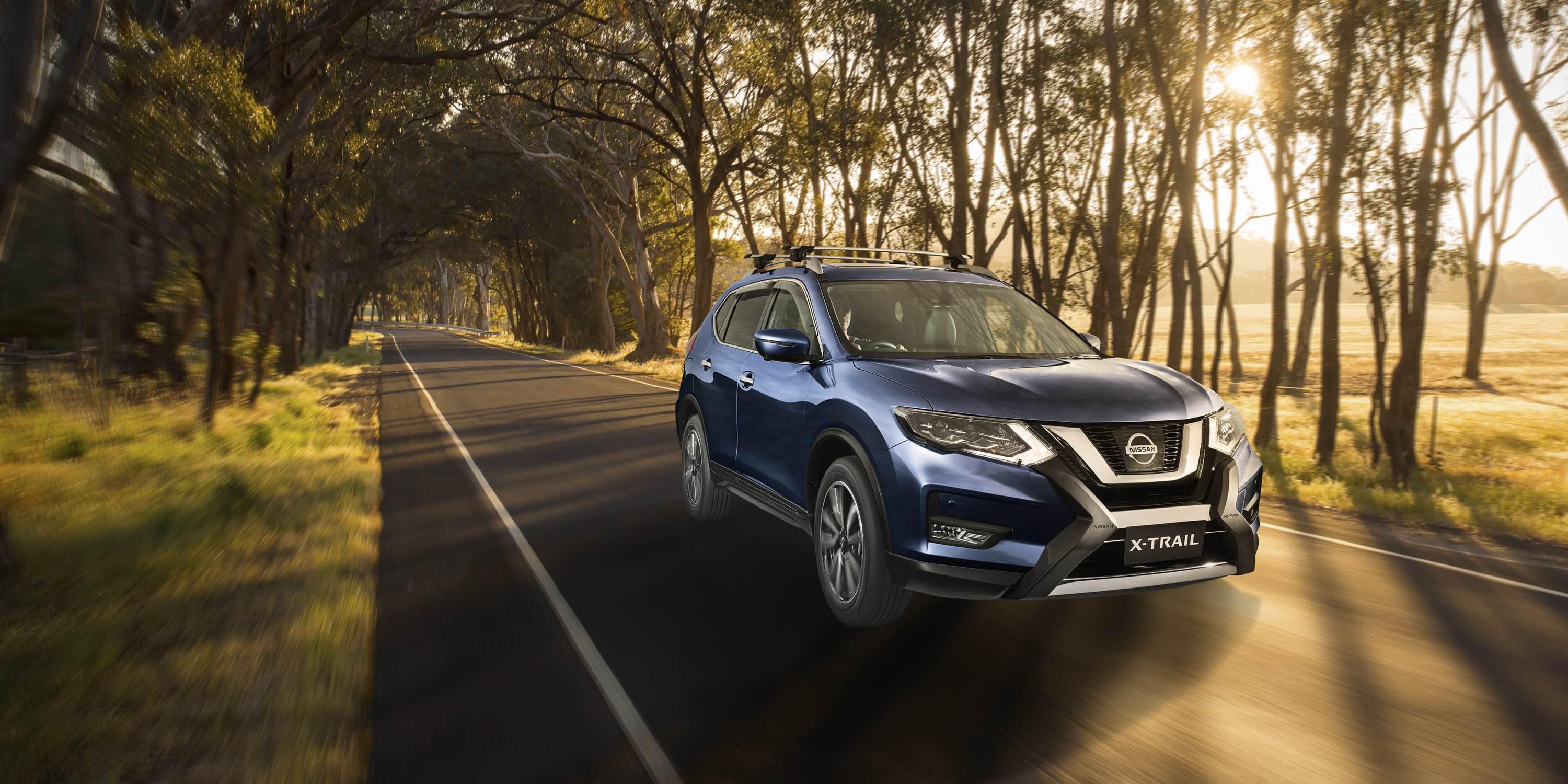 Marine Blue X-TRAIL driving across Australian countryside
