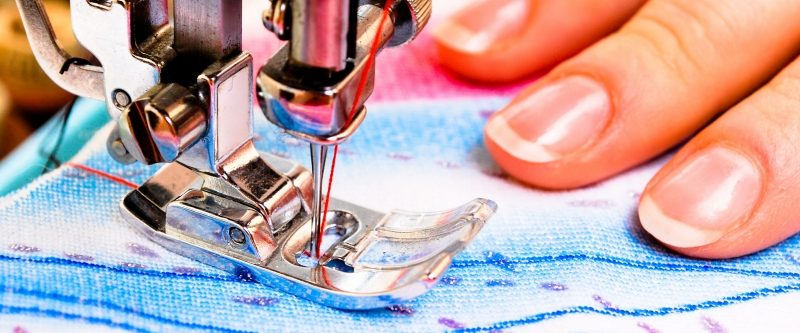 Close up of woman using sewing machine