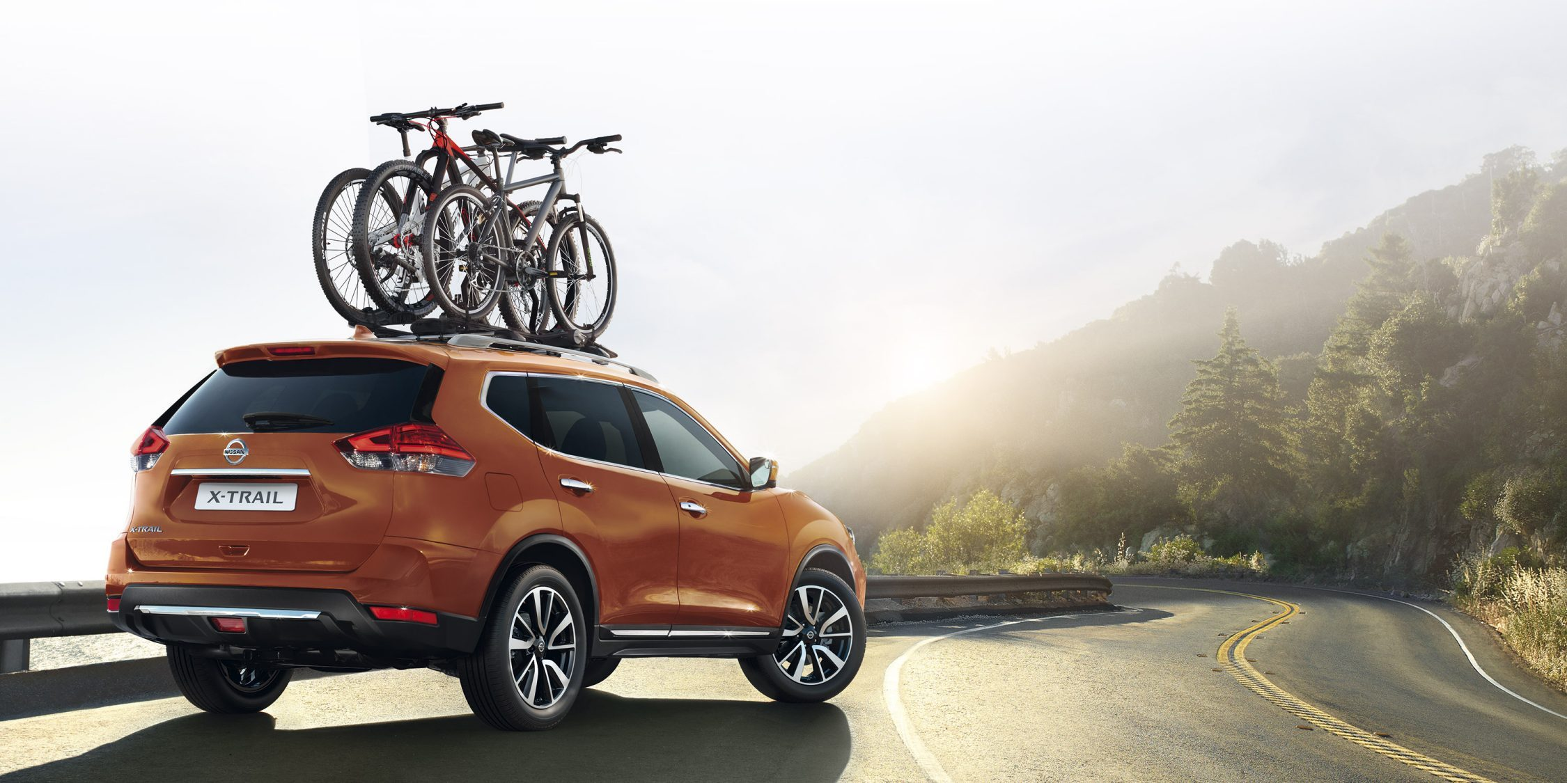 Nissan X-Trail on mountain road with bikes on roof