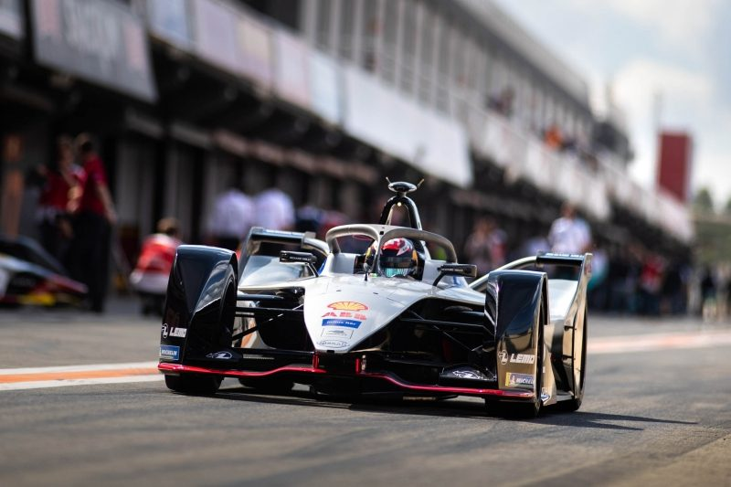 Nissan Formula E Racer accelerates out of pit area front view